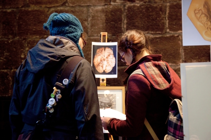 Members of the public interacting with displays produced by Art Gallery and Museum Studies students at the Chetham's Library exhibition, December 2015